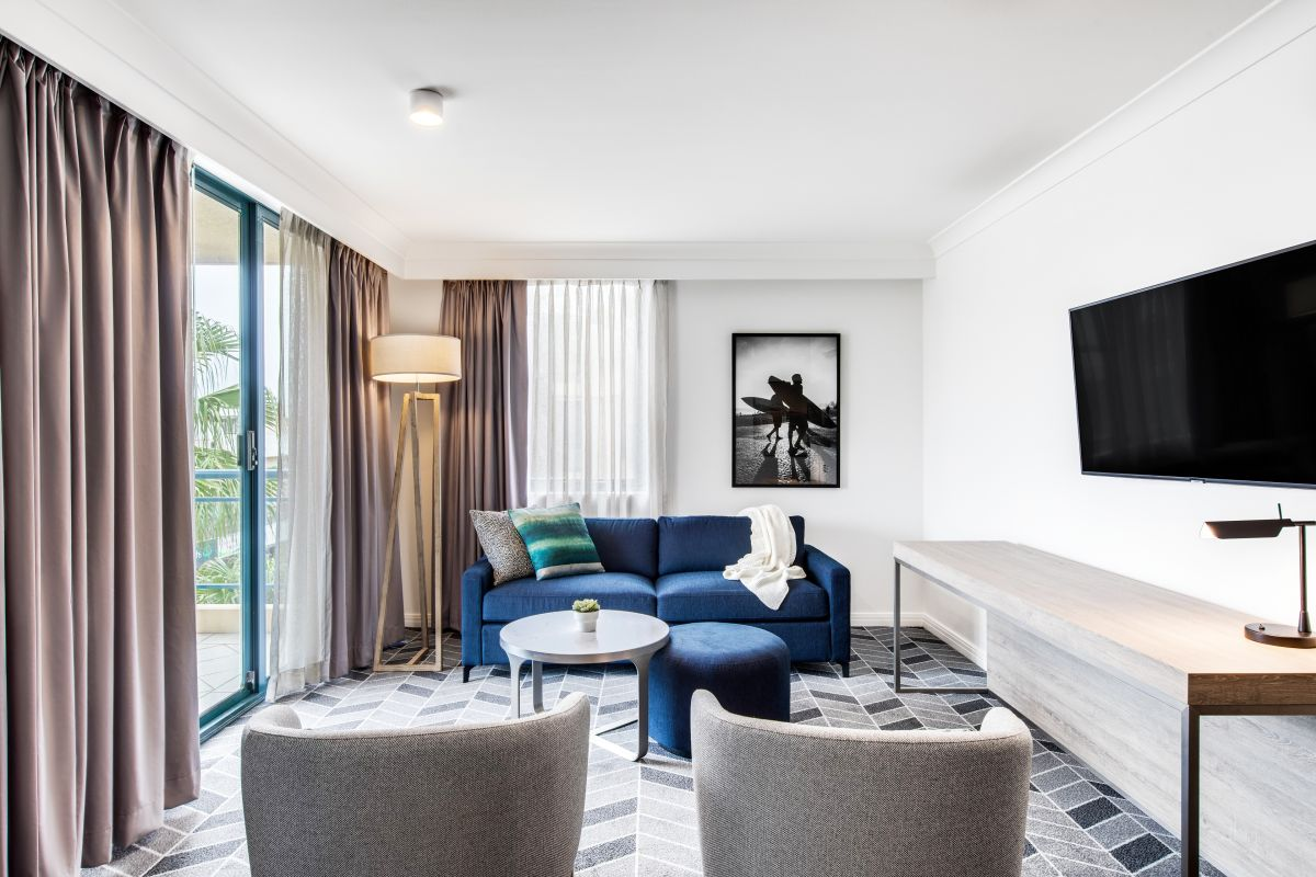 The lounge room in this two-bedroom apartment features a grey and navy colour palette.